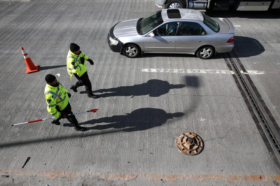 State Police walked past a manhole cover on I-93.